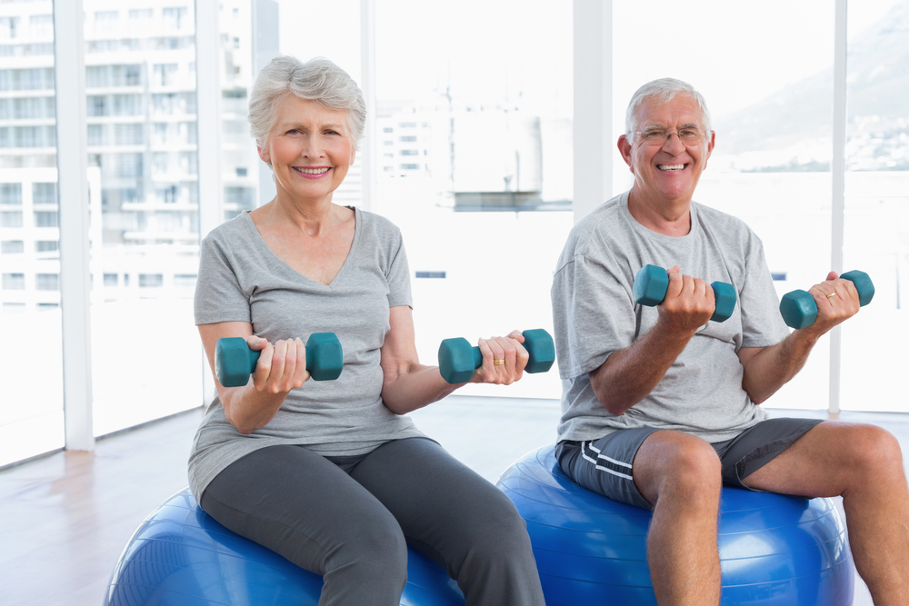 Senior couple exercising on fitness balls with dumbbells at the UAB Med West cardiac rehab.